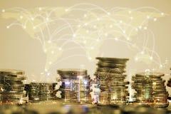 Dubbele blootstelling van muntstukstapel met stadsachtergrond en wereldkaart Stock Foto