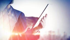 Dubbele blootstelling van stad en handen die digitale tablet gebruiken Stock Fotografie