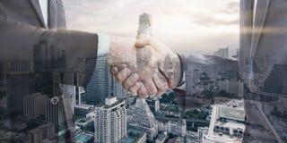 Dubbele blootstelling van twee zakenman het schudden handen met stad in bedelaars stock foto's