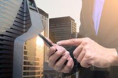Dubbele blootstelling van zakenman die telefoon met stads scape nacht met behulp van stock afbeeldingen
