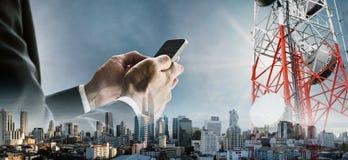 Dubbele blootstellingszakenman smartphone met cityscape gebruiken, en telecommunicatietorens die stock foto's