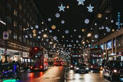 Dubbele Dek rode bussen, zwarte die cabines en auto's op de Straat van Oxford, Londen, met Kerstmislichten wordt verfraaid Stock Foto
