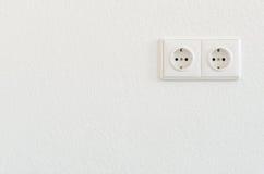 Dubbele elektrocontactdoos op wit behang Stock Foto's