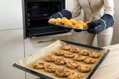 Dubbele last: bedrijfsvrouwenbaksel cupcakes in de keuken stock afbeelding