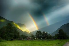 Dubbele regenboog in bergen Stock Afbeelding