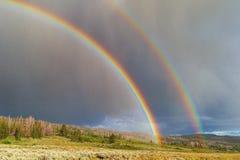 Dubbele regenboog met zon en regen stock afbeeldingen