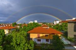 Dubbele regenboog over de stad stock afbeeldingen