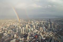 Dubbele Regenboog over de stad in - Antenne Stock Afbeelding