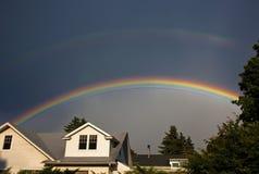 Dubbele regenboog over huizen Stock Afbeelding