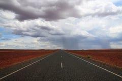 Dubbele steegweg in een rode woestijn die in de afstand disapearing Stock Foto