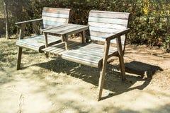 Dubbele stoelen die zich in de tuin met schaduwen bevinden Stock Foto's
