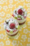 Dubbele zachte cake met bes in glazen op gele B Stock Foto