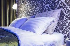 Dubbelsäng med kuddar i inre av det moderna sovrummet i vindlägenhet i ljus färgstil av dyra lägenheter i neonljus arkivbild