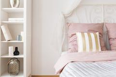 Dubbelsäng med rosa sängkläder arkivfoto