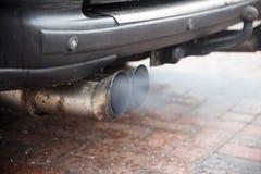 Dubbelt avgasrör från en äldre bil med dieselmotorn blåser ut gummin fotografering för bildbyråer