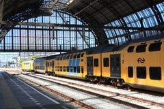 Dubbelt däcksdrev som låter vara den Amsterdam stationen Arkivfoton
