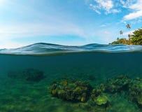 Dubbelt landskap med havet och himmel Kluvet foto med den tropiska ön och den undervattens- korallreven Royaltyfria Bilder