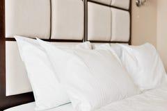 dubbelt modernt för sovrum Bekväma mjuka vitkuddar på en säng Inre rum av en lägenhet eller ett hotell Arkivbilder