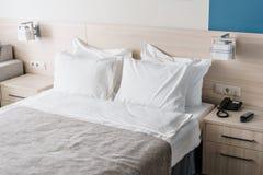 dubbelt modernt för sovrum Bekväma mjuka vitkuddar på en säng Inre rum av en lägenhet eller ett hotell Royaltyfria Foton