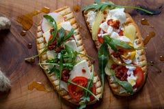 Dubbelt rostat bröd med ägget, aragula, tomat och ost, bröd för franskt rostat bröd med veggies Royaltyfri Foto