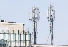 Dubbelt telekommunikationtorn på byggnaden Arkivbilder