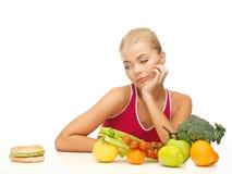 Dubbio della donna con i frutti e l'hamburger fotografia stock