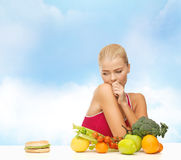 Dubbio della donna con i frutti e l'hamburger immagini stock