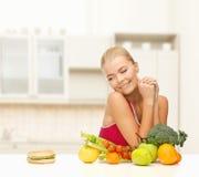 Dubbio della donna con i frutti e l'hamburger immagini stock libere da diritti
