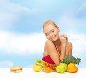 Dubbio della donna con i frutti e l'hamburger immagine stock libera da diritti