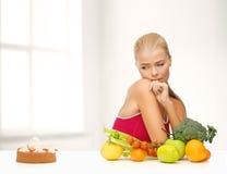 Dubbio della donna con i frutti e la torta fotografie stock libere da diritti