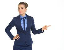 Dubbio della donna di affari che indica sullo spazio della copia fotografia stock