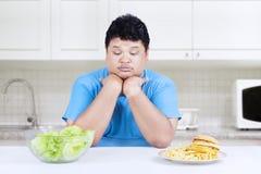 Dubbio della persona per scegliere gli alimenti immagine stock