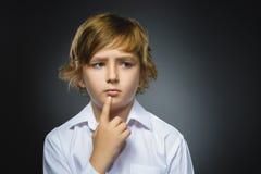 Dubbio, espressione e concetto della gente - ragazzo che pensa sopra il fondo grigio fotografia stock