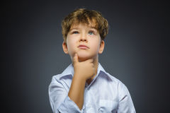 Dubbio, espressione e concetto della gente - ragazzo che pensa sopra il fondo grigio immagine stock