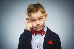 Dubbio, espressione e concetto della gente - ragazzo che pensa sopra il fondo grigio immagine stock libera da diritti