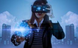 Dubbla exponering-framtid VR hörlurar med mikrofon, kvinnaaffär i dräkter som använder fingrar, erfar bästa teknologi från modern arkivbild