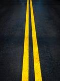 Dubbla gula linjer på vägbakgrund Royaltyfri Fotografi