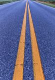 Dubbla gula linjer som delar vägen arkivfoto