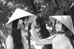 Dubbla studenter hjälper varje koniska hattar Royaltyfria Bilder