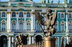 Dubblett-hövdad örn i den imperialistiska kronan på bakgrunden av eremitboningen (vinterslott) i St Petersburg Royaltyfri Fotografi