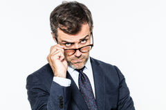 Dubious far-sighted businessman holding down eyeglasses looking concerned Stock Images