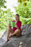 Dubious 20s girl reading a summer book under a tree. Outdoors reading - young suntanned blond woman questioning her summer book,reading on a giant stone in the Stock Photo