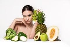 Dubitando la bella ragazza castana con luminoso componga, con la frutta e le verdure sulla tavola Forma fisica, dieta, salute e immagini stock libere da diritti