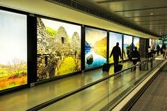 Dublin Airport folk, passagerare som reser med resväskor på gångbanarulltrappan i rörelse med markerade bilder av Irland i t Royaltyfria Foton