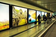 Dublin Airport people, passengers travelling with suitcases on walkway escalator in motion with highlighted images of Ireland in t Royalty Free Stock Photos