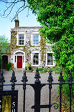 Dublin house. House facade with red door and green trees. Spring. Dublin, Irland Stock Images