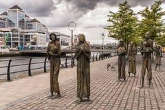 Great Irish Famine statue in Dublin, Ireland. Dublin, Ireland - August 7, 2017: Great Irish Famine bronze statue set on Custom House Quay along Liffey River in Royalty Free Stock Image