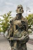 Great Irish Famine statue in Dublin, Ireland. Dublin, Ireland - August 7, 2017: Great Irish Famine bronze statue set on Custom House Quay along Liffey River in Royalty Free Stock Photo
