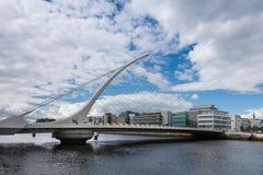 Samuel Beckett Bridge, Dublin Ireland. Dublin, Ireland - August 7, 2017: Modern Samuel Beckett bridge under blue-white cloudscape with new office buildings in stock images