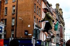 Dublin Ireland - 20 de fevereiro de 2018: Um executor da rua está em um unicycle que faz um desempenho em Grafton Street rua imagens de stock